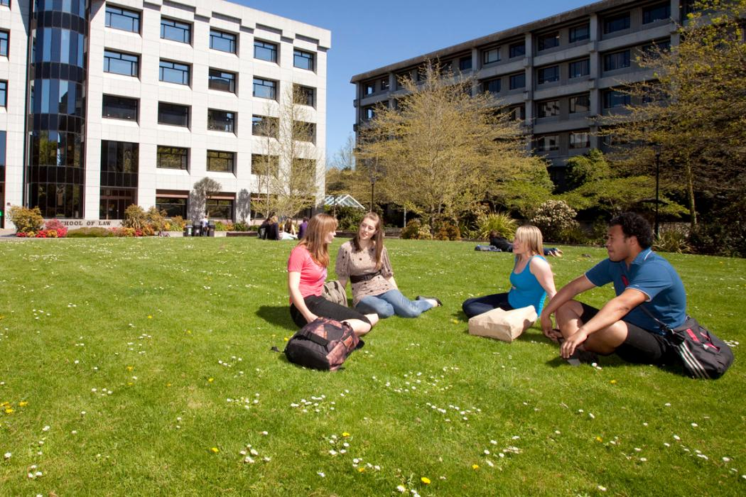 group of students sitting on lawn in front of business and law building