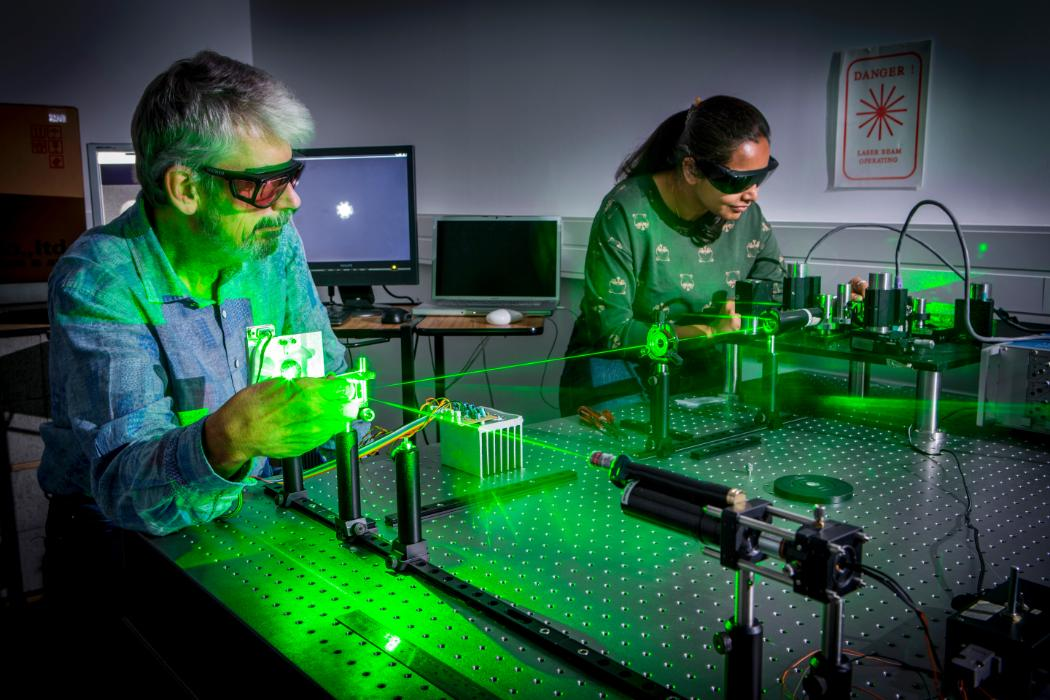 lecturer and postgrad in optics lab with laser